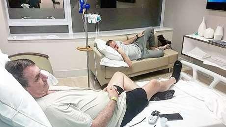 Jair Bolsonaro assiste tv ao lado do filho, Carlos, no quarto do Hospital Vila Nova Star, onde se recupera de cirurgia