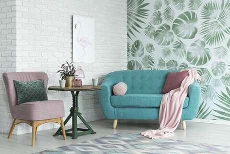 9. Sala de estar decorada com sofá azul e papel de parede com folhagens – Foto: Habitissimo