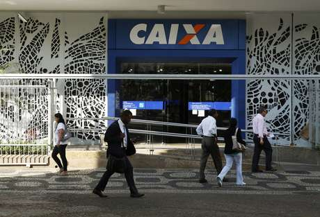 Pessoas passam pela frente de agência da Caixa Econômica Federal, no Rio de Janeiro. 20/8/2014. REUTERS/Pilar Olivares