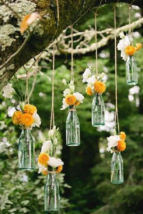 22. Decoração com garrafas decoradas suspensas ideal para festas de casamento