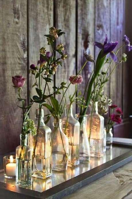 23. Decoração feita com garrafas decoradas de vidro como vasos de flores