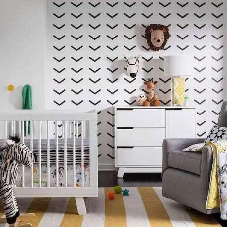 52. Parede decorada com fita isolante preta para quarto de bebê com tapete listrado – Foto: Yelp