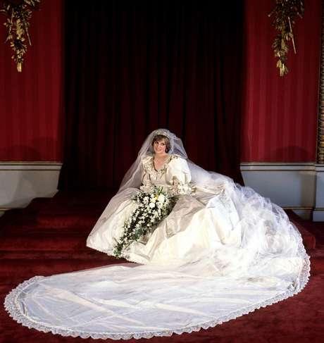 Princesa Diana - O vestido de noiva da princesa Diana, criado pelo casal de estilistas David e Elizabeth Emanuel, foi bordado com madrepérolas e lantejoulas no colo, nas manga e na cintura. O modelo foi feito de tafetá de seda, mesmo tecido do véu