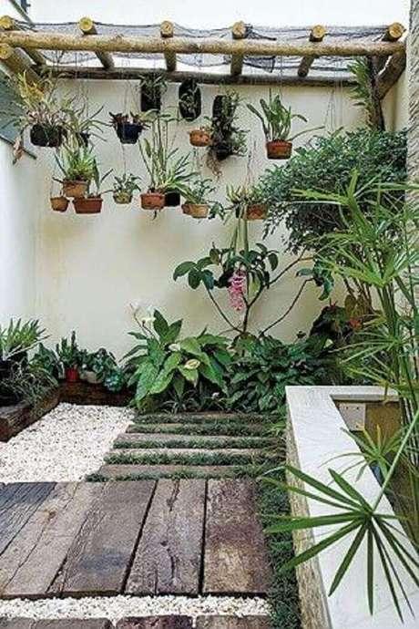 48. Área de lazer pequena com pergolado de madeira e grama do tipo preta. Fonte: Revista Casa e Jardim