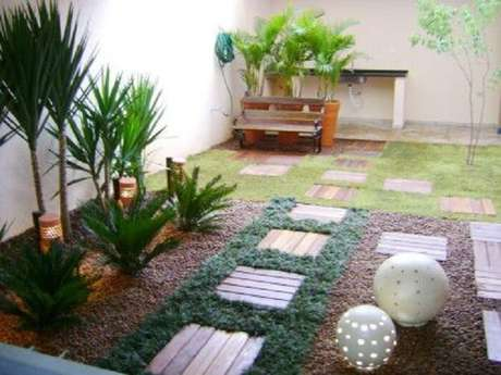 37. Área de lazer pequena com piso de madeira e grama preta. Fonte: Pinterest