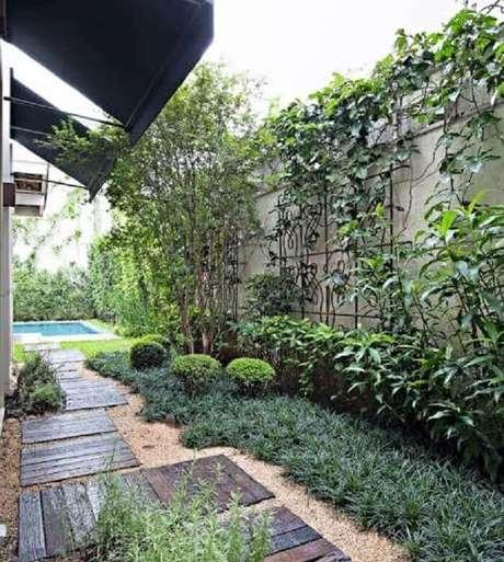 16. Área externa com chão forrado com grama preta e placas de madeira. Fonte: Casa e Jardim