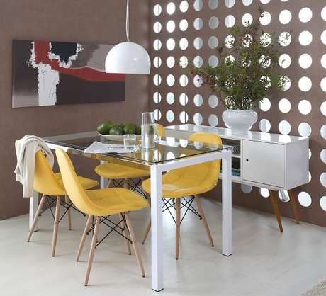 11. Sala de jantar com mesa de tampo de vidro e cadeira eames amarela estofada. Fonte: Pinterest