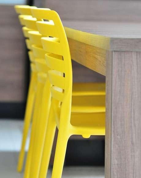 1. Ambiente com cadeira amarela de polipropileno. Projeto por Condecorar Arquitetura e Interiores