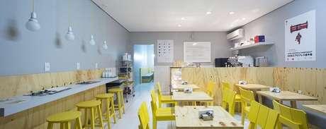 12. Ambiente comercial com cadeira amarela e mesas de madeira. Projeto por Kali Arquitetura