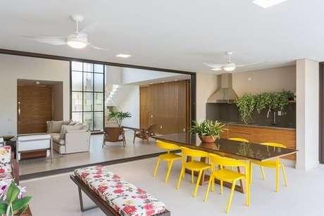 9. Área externa com mesa quadrada e cadeira amarela. Projeto por Jannini Sagarra Arquitetura