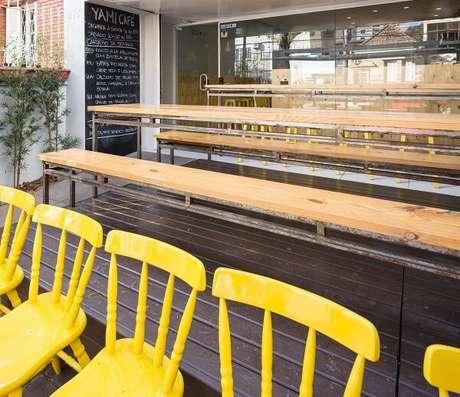 14. Área externa gourmet com cadeira amarela de madeira. Projeto por Kali Arquitetura