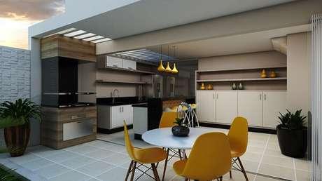 15. Área gourmet com mesa redonda branca e cadeira amarela. Projeto por Arquiteto Caio Pelisson