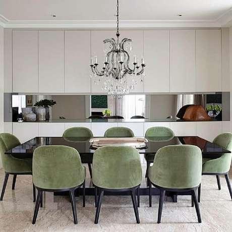17. Decoração com cadeira estofada verde musgo para sala de jantar sofisticada com lustre candelabro – Foto: Paula Magnani