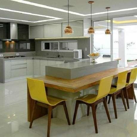 21. Cozinha com bancada de madeira embutida e cadeira amarela. Fonte: Revista Viva Decora