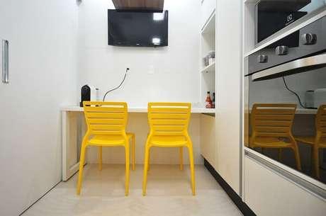 22. Cozinha compacta com balcão branco e cadeira amarela. Projeto por Condecorar Arquitetura e Interiores