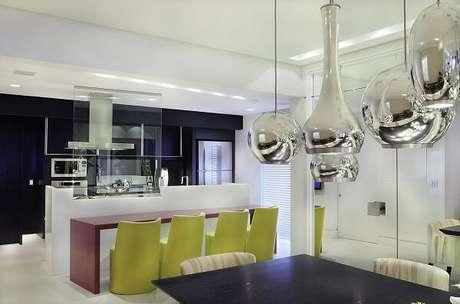23. Cozinha gourmet com bancada vermelha e cadeira amarela. Projeto por Moreno Interiores