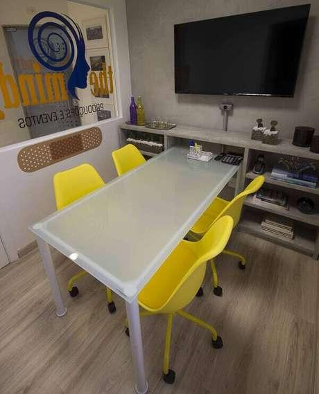 7. Sala de reunião decorada com mesa branca e cadeira de escritório amarela. Projeto por MIS Arquitetura e Interiores