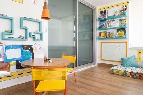 24. Espaço infantil com prateleira azul e cadeira amarela com detalhes em laranja. Fonte: Revista Viva Decora