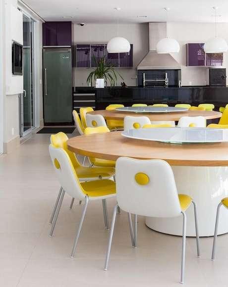 25. Mesa redonda branca com cadeira amarela estofada. Projeto por Olegário de Sá & Gilberto Cioni