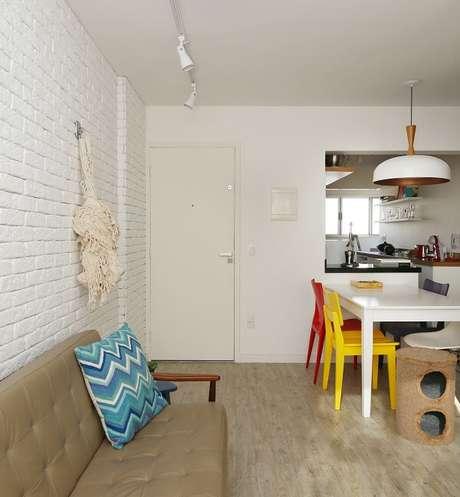 26. Cadeira amarela e vermelha compõem a decoração da sala de jantar. Projeto por SP Estudio
