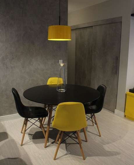 27. Mescle tons na sala de jantar usando uma cadeira amarela eiffel e preta estofada. Projeto por Amanda Pagliarini Macedo