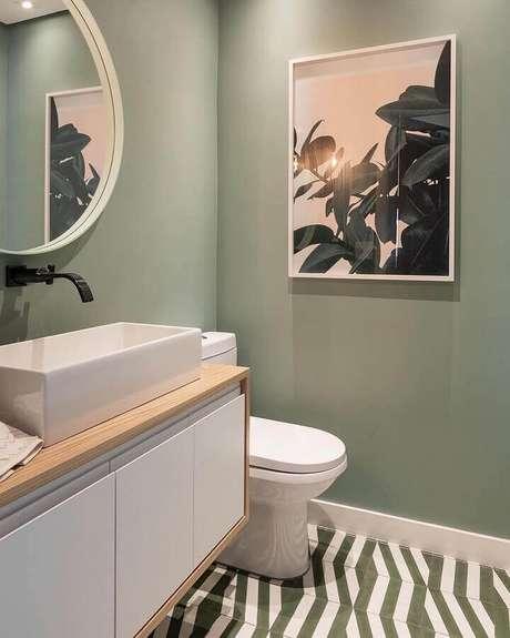 42. Decoração para banheiro pequeno com parede verde musgo e espelho redondo – Foto: Maurício Arruda