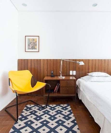 33. Quarto de casal com cadeira amarela posicionada ao lado da cama. Projeto por Felipe Hess