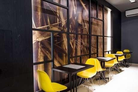 37. Restaurante com mesa preta e cadeira amarela. Projeto por Mariana Borges e Thaysa Godoy