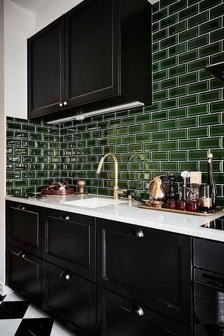 51. Cozinha planejada com armários pretos e revestimento verde musgo – Foto: Planeta Deco