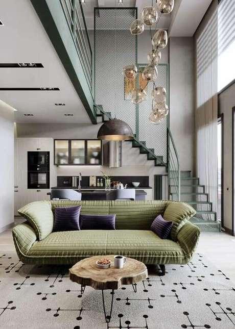 52. Sala com pé direito alto decorada com sofá verde musgo e luminária de teto moderno – Foto: Behance