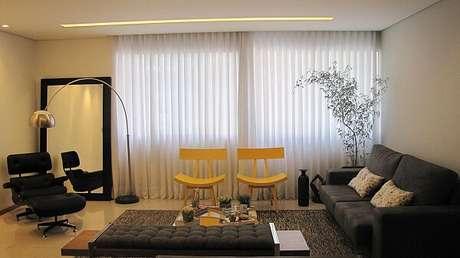 38. Sala de estar ampla com cadeira amarela e sofá preto. Projeto por Danielly Porcina Medeiros Silva