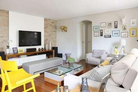 39. Sala de estar com sofá branco e cadeira amarela. Projeto por Maíra Marchió
