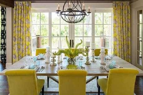 48. Sala de jantar com cadeira amarela estofada e mesa de madeira. Fonte: Pinterest