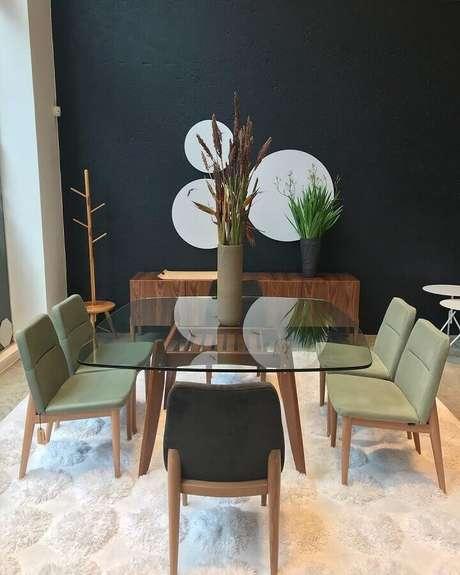 54. Sala de jantar moderna decorada com espelhos redondos em parede preta e cadeiras verde musgo para mesa de vidro – Foto: Gabriela Toledo Arquitetura