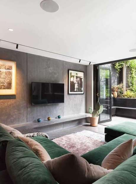 57. Sala moderna decorada com parede de cimento queimado e sofá verde musgo de canto – Foto: Pinterest