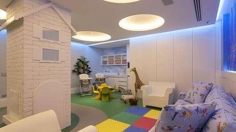 42. Sofá azul com bonequinhos e cadeira amarela no espaço de brinquedoteca. Projeto por Jayme Bernardo Arquitetura e Design