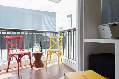 45. Varanda compacta com mesa de centro e cadeiras no tom amarelo e vermelho. Projeto por Renata Cáfaro