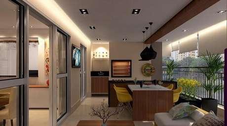 46. Varanda gourmet com mesa de madeira e cadeira amarela. Projeto por Raduan Arquitetura