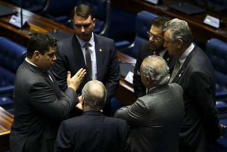 Opresidente do Senado, Davi Alcolumbre, conversa com os senadores Tasso Jereissati e Flavio Bolsonaro em sessão de votação da reforma da Previdência.