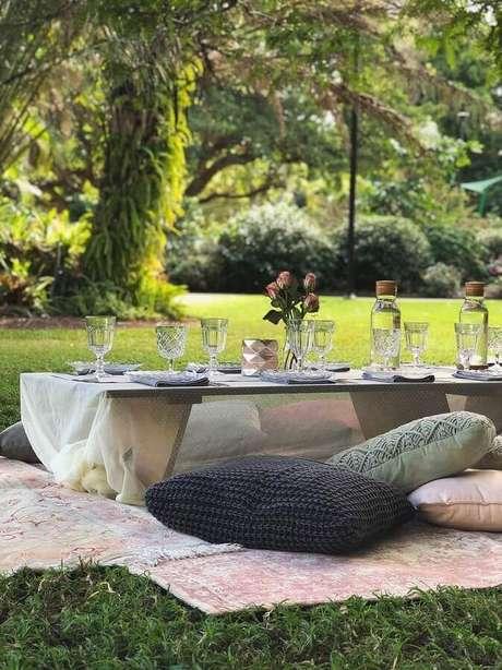 12. Decoração simples para festa picnic com almofadas e mesa baixa de madeira – Foto: Pinterest