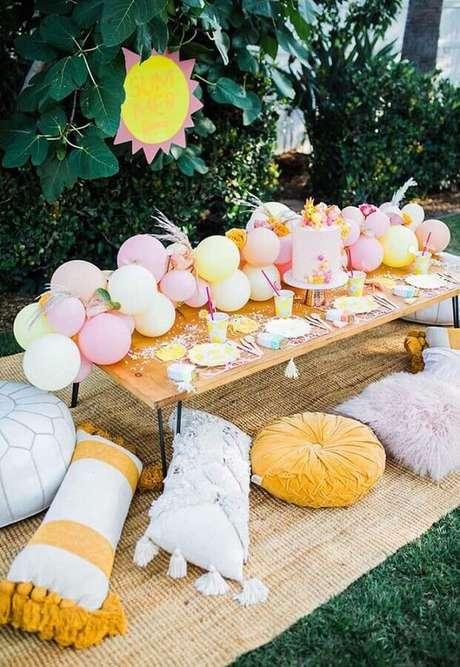 15. Decoração de aniversário piquenique com arranjo de balões e almofadas diferentes – Foto: