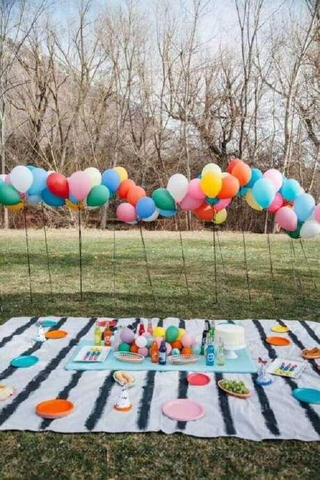 18. Arranjo de balões e toalha listrada para festa piquenique com pratos coloridos – Foto: Ideias Decor