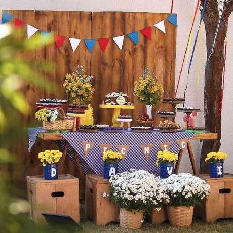 20. Arranjo de flores e toalha xadrez azul para aniversário piquenique com móveis de madeira – Foto: Vila Afetiva Festas