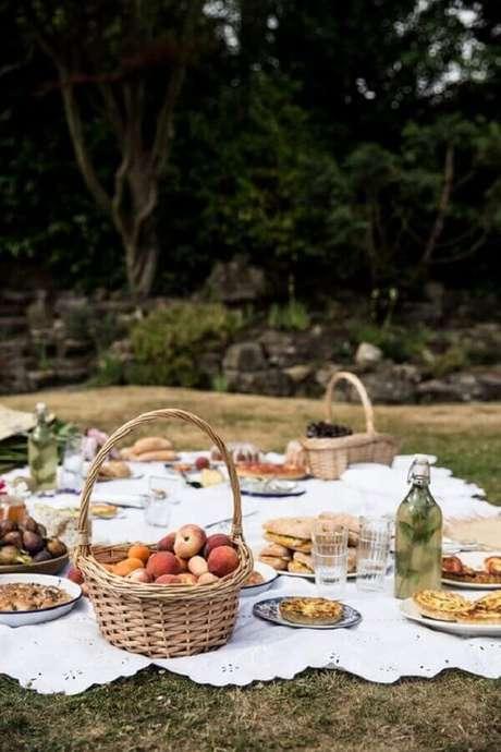 32. Decoração com cesta de piquenique com frutas e toalha branca – Foto: La Coqueta Blog