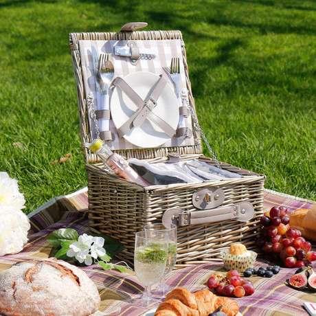 34. Cesta de piquenique com talheres e pratos para festa com pães e frutas – Foto: Pinosy