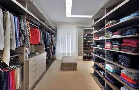 21. Closet feminino amplo com puff marrom – Por: Bender Arquitetura