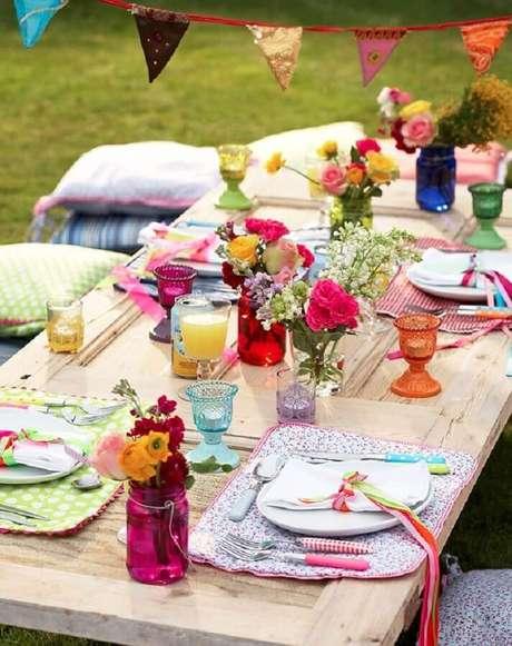 42. Almofadas e vasinhos coloridos de flor para decoração simples de festa piquenique – Foto: Pinterest