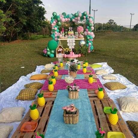 43. Decoração colorida para aniversário piquenique com jarros em formato de abacaxi e pallets no lugar da mesa – Foto: Pinosy