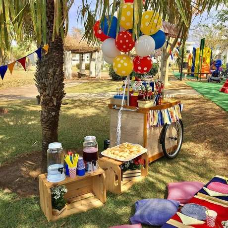 69. Decoração rústica para festa picnic com balões e almofadas coloridas e caixotes de madeira – Foto: Daniela Chiessi