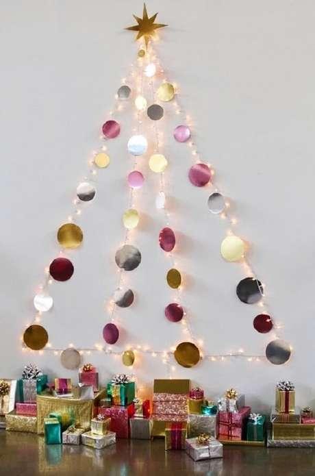 45. A árvore de Natal na parede foi feita com pisca pisca e bolinhas metálicas. Fonte: Pinterest